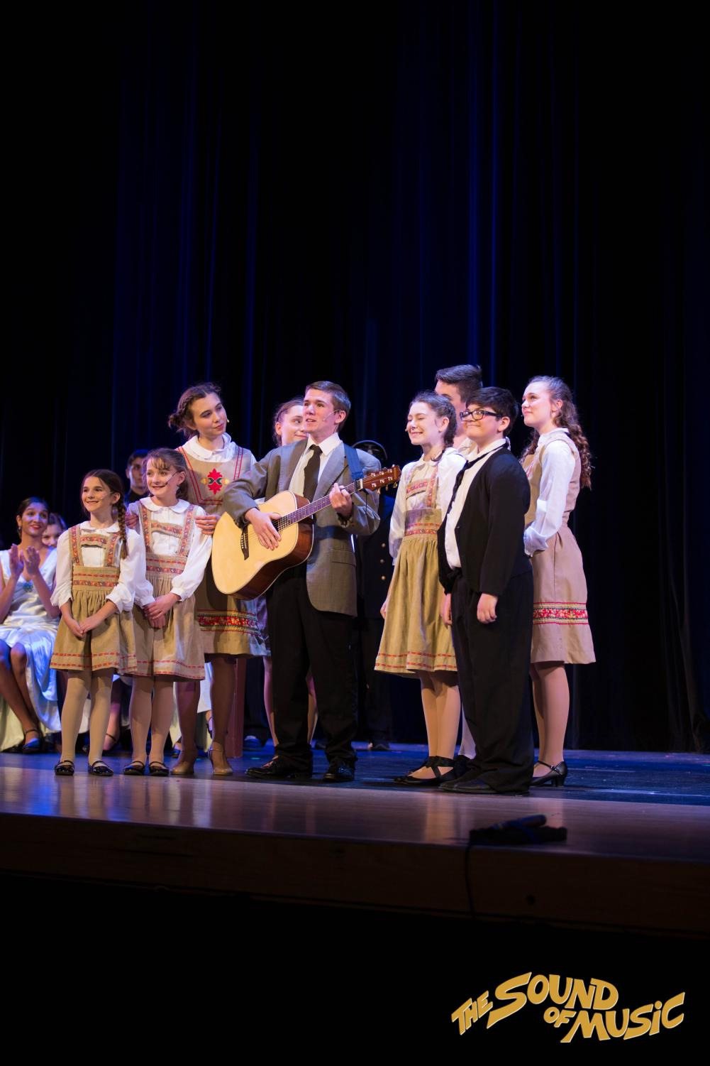 Senior Michael O'Connor, playing   Captain Georg von Trapp, pictured singing accompanied by acoustic guitar.