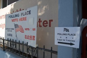 Signs in different languages point attention to a polling place.