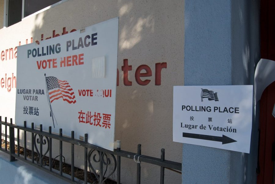 Signs+in+different+languages+point+attention+to+a+polling+place.