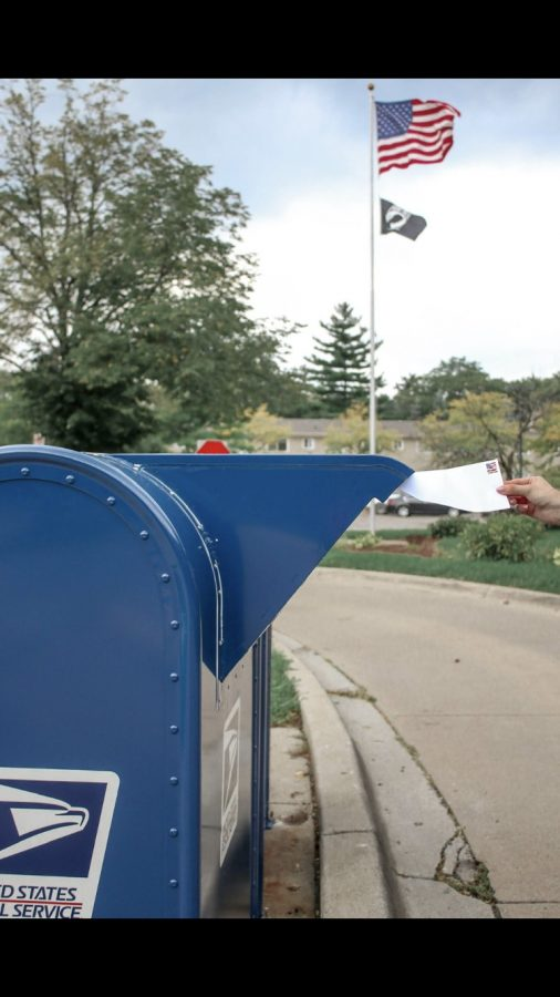 A person putting their mail in ballot for the election in their mailbox.