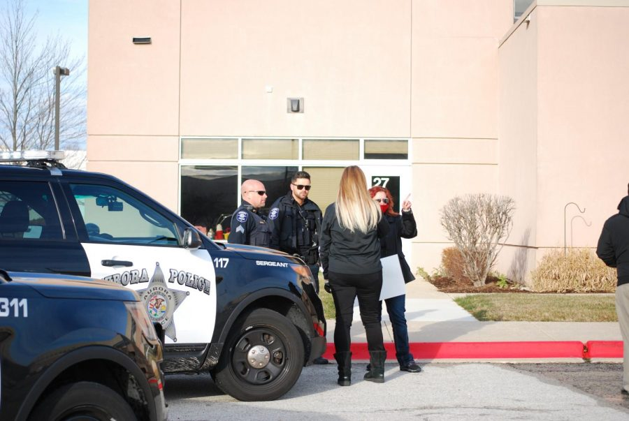 The organizers of the event speak to the Aurora Police Department before the event begins.
