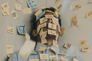 A man lays down on the floor, with a flock of sticky notes with reminders surrounding him.