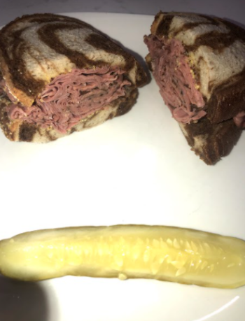 Schmaltz Deli's Hot Pastrami sandwich with a side of a dill pickle. Each item is made with love, and probably a reoccurring sound of Bubbies voice telling them to