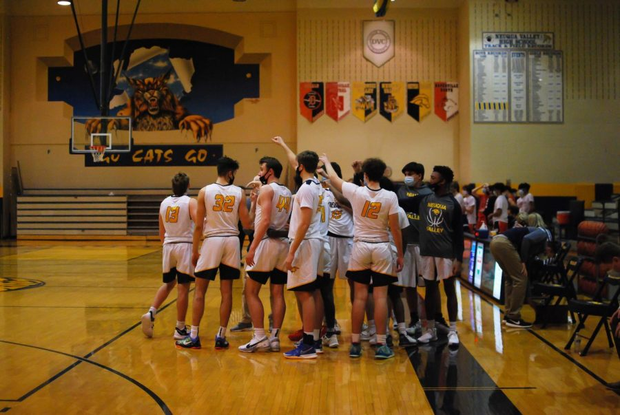The boys varsity basketball team huddles up at halftime