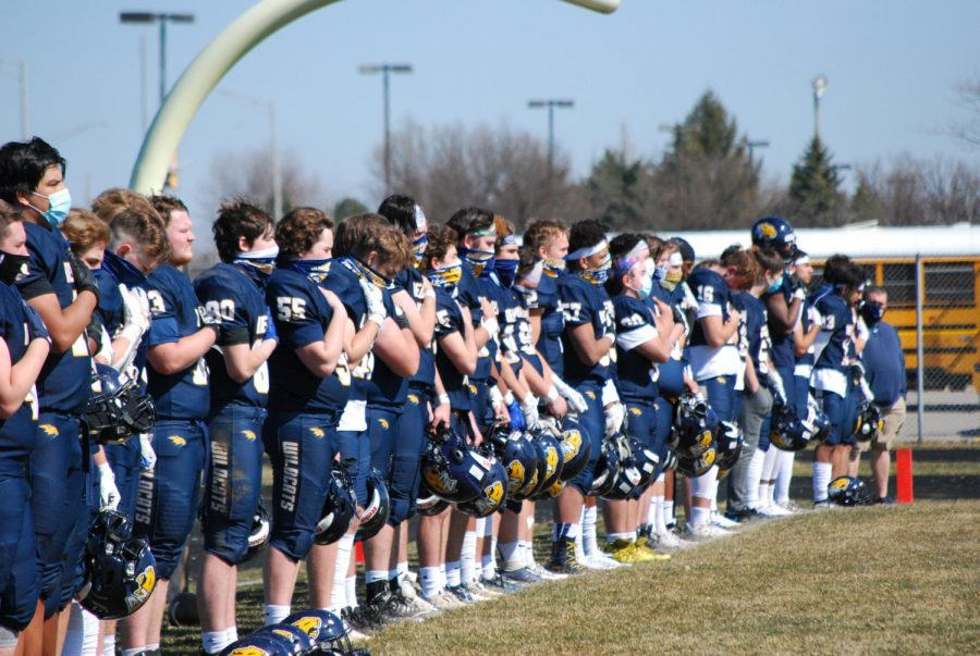 Neuquas Varsity football team stands for the National Anthem.