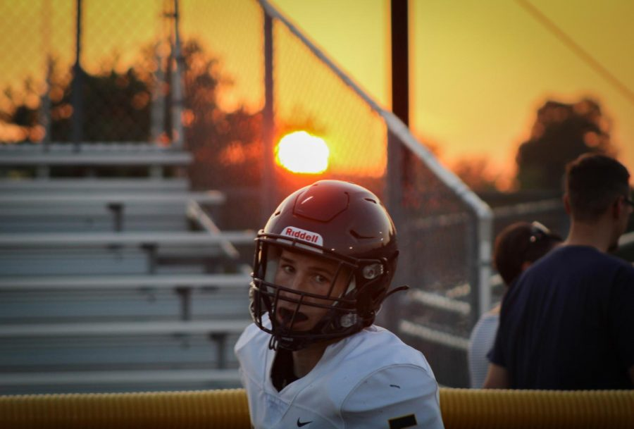 Football players modeled on the field during golden hour.