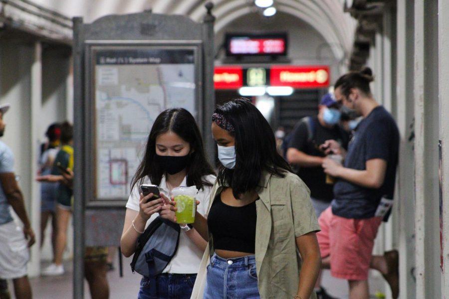 Teens walk throughout the underground station.