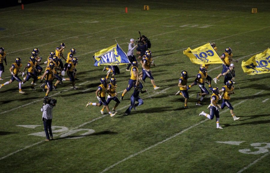 Neuqua Valley Gold Rush running through the field with the players.