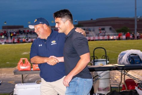 Neuqua Alumni Joey Rhattigan smiles during the Hall of Fame Induction Ceremony at Neuquas homecoming football game.