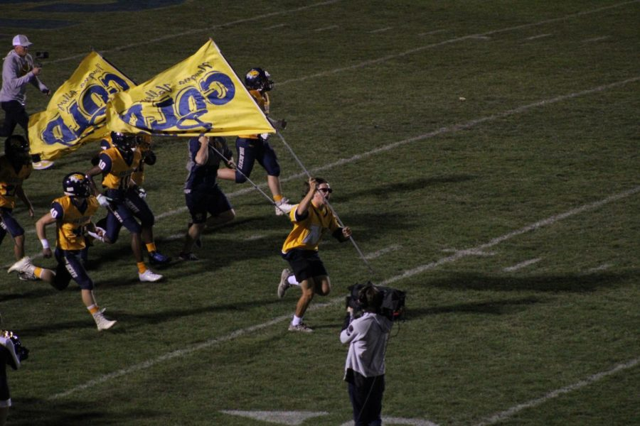 Richie Mattia, a senior, in front of all the players carrying the Neuqua Valley Gold Rush flag.